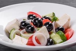 verse heerlijke Griekse salade met tomaat, komkommer, uien en olijven met olijfolie foto
