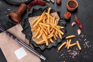 Lekkere gebakken frietjes met zout en kruiden op een donkere achtergrond foto