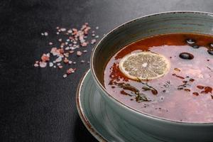 heerlijke verse warme soep met tomaat en vlees in een keramische plaat. mengelmoes soep foto