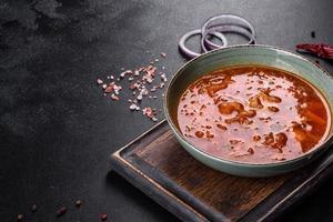heerlijke verse warme borsjt met tomaat en vlees in een keramische plaat foto