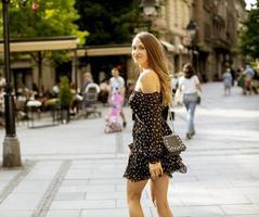 jonge langharige brunette vrouw die op straat loopt foto
