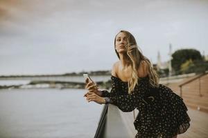 jonge langharige brunette vrouw die aan de rivier staat? foto