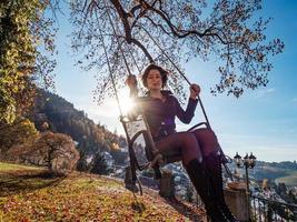een jong meisje zwaait op een schommel. zonnige dag. foto