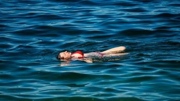 een jong meisje zwemt in het kristalheldere water van een bergmeer. foto