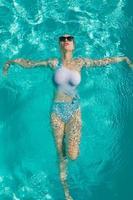 jonge mooie sexy meid die geniet van zwemmen in het privézwembad en ontspannen in de zon foto
