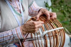 oude vrouw in klederdracht maakt lokale rieten mand. traditioneel handwerkconcept. letland - afbeelding foto