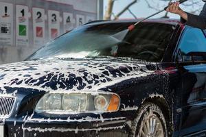 auto zonder aanraking wassen self-service. wassen met water en schuim. foto