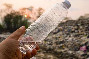 plastic fles in mensenhand op grote huisvuilstapel en vervuilingsachtergrond foto