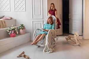 een jonge vrouw zit in een schommelstoel. vlakbij zit een dochter in een feestelijke jurk, een afgestudeerde tiener. afstuderen op school, universiteit. familie. foto