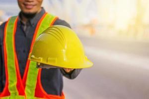 close-up ingenieur houd veiligheidshelm bouwachtergrond vast foto