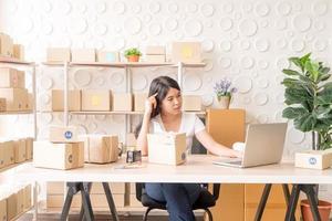 Aziatische vrouw bedrijfseigenaar die thuis werkt met verpakkingsdoos op de werkplek - online winkelen mkb-ondernemer of freelance werkconcept foto