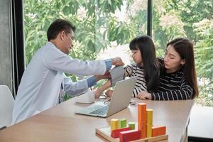 een moeder en dochter examenafspraak met een Aziatische mannelijke arts. foto