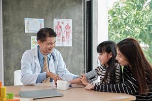 een moeder brengt haar zieke dochter naar een examenafspraak met een Aziatische mannelijke arts op de afdeling kindergeneeskunde van een kinderkliniek. om ziekten te behandelen en te overleggen over de gezondheid van het gezin. foto
