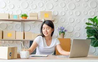jonge Aziatische vrouw startende kleine ondernemer die met digitale tablet op de werkplek werkt - online verkoop, e-commerce, verzendconcept foto