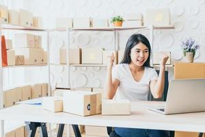 jonge vrouw blij na nieuwe bestelling van klant, ondernemer thuis - online winkelen mkb-ondernemer of freelance werkconcept foto