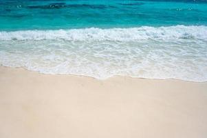 heldere zeegolven en wit zandstrand in de zomer. foto