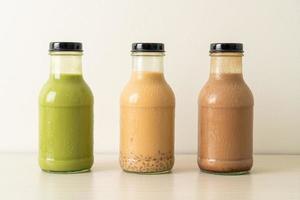 matcha groene thee latte, chocolade en melkthee met puddinggelei in glazen fles op tafel foto