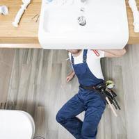 sanitair technicus liggende gootsteen. mooi fotoconcept van hoge kwaliteit foto