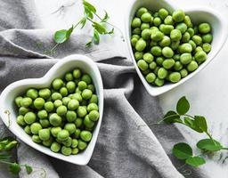 groene erwten in hartvormige kommen op een stoffenachtergrond foto
