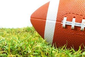 Amerikaanse voetbalbal op groen gras dat op witte achtergrond wordt geïsoleerd foto