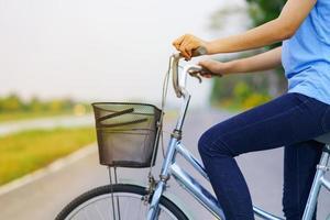 meisje met fiets, vrouw fietsen op de weg in een park foto