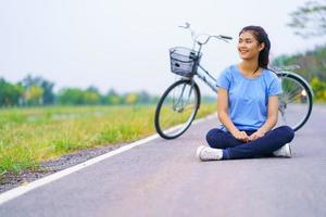 meisje met fiets, vrouw zittend op de weg in het park en een fiets foto