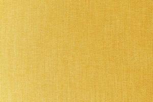 close-up gele of gouden mosterd stof oppervlaktetextuur voor background foto