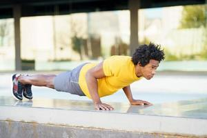 zwarte man doet triceps duik oefening op straat bankje. foto