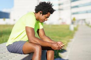 zwarte man raadpleegt zijn smartphone met een oefen-app foto