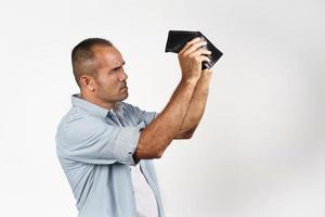 boos volwassen man vasthouden en kijken in zijn lege portemonnee. foto