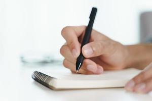 close-up van man handen opschrijven op het notitieblok, notebook met pen. foto