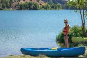 vrouw in een reddingsvest die naast een kano bij het water staat foto