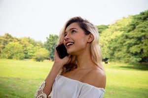 portret van een lachende mooie vrouw die sms't en praat met haar telefoon foto