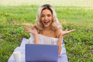 mooie vrouw online sociale media met een laptop buiten in een park foto