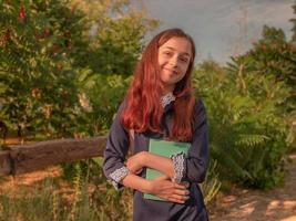 schoolmeisje in een schooljurk met een notitieboekje en een rugzak buitenshuis foto