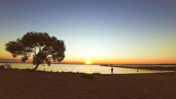 persoon op afstand bewondert zonsondergang en maakt foto