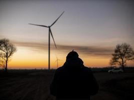 silhouet van een man bij zonsondergang die een foto maakt van windturbines