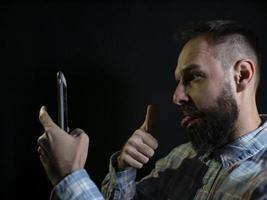 modieuze man met een baard grimassen en neemt een selfie aan de telefoon foto