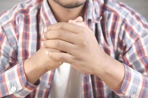 handen van doordachte jonge man close-up foto