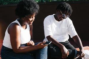 twee gelukkige Afro-Amerikaanse vrouwen communiceren en lachen op straat foto