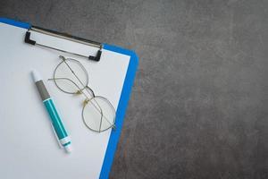 bril en notitieboekjes worden op de grond gelegd foto