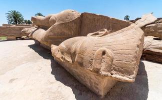oud standbeeld van farao ligt op de grond in een karnak-tempel foto