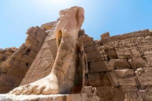 voeten van een oud standbeeld van farao in de karnak-tempel in luxor foto
