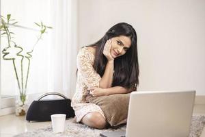 Indisch mooi jong meisje dat laptop thuis gebruikt foto