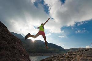 springend meisje terwijl hij in de bergen rent foto