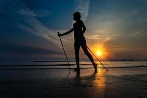 mager meisje bij zonsopgang op het strand naar de zee met nordic walki foto