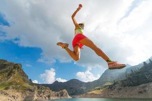 springend meisje terwijl hij in de buurt van een bergmeer rent foto
