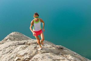 Skyrunner-meisje rent op een stenen rug over een meer foto