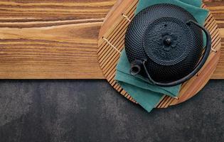 zwarte gietijzeren theepot met kruidenthee op donkere stenen achtergrond foto
