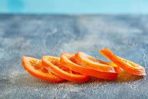 schijfjes gedroogde sinaasappels of mandarijnen op een blauwe achtergrond foto